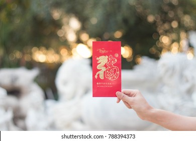 Hand holding red envelope to give in chinese new year.