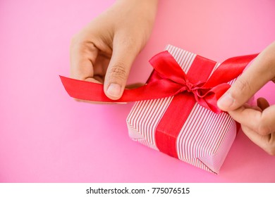 Hand holding a red gift box on pink background .Christmas, Boxing day  and New year concept.
