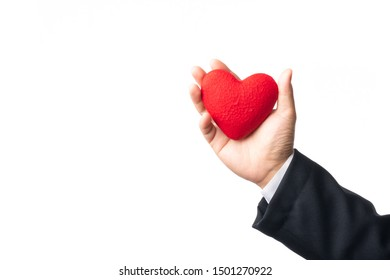 Hand holding a red heart on a white background.