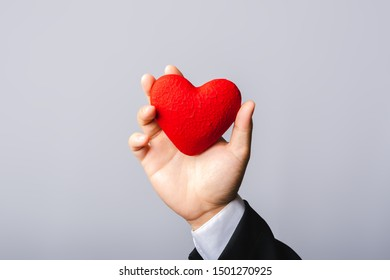 Hand holding a red heart on a gray background.