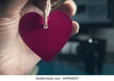 hand holding a red heart on defocused