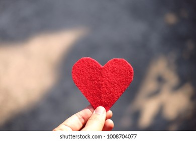 Hand holding Red heart shape in beautiful natural blurred Green bokeh of nature background. Valentine day holiday concept. Copy space