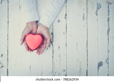 hand holding a red heart, valentine's day love, vintage tone