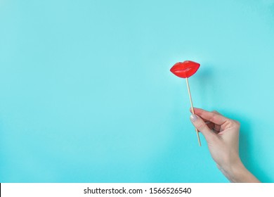 Hand holding Red Lips Lollipop. Lollipop candy in the shape of red lips, minimal concept composition on blue background, copy space.