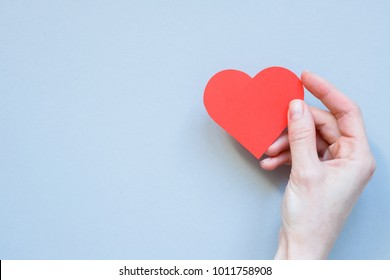 Hand holding red paper heart on the blue background. With copy space.