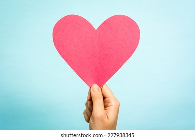 Hand holding red paper love heart shape on blue background. Love concept.