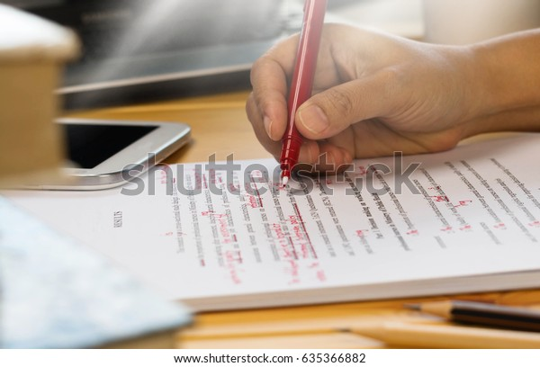 hand holding red pen over proofreading text in office