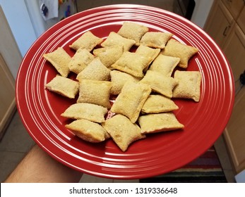 hand holding red plate of frozen pizza rolls