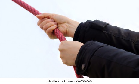 A hand holding a red rope.