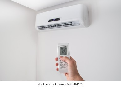 Hand holding remote control, adjusting temperature of air conditioner mounted on a white wall. Indooor comfort temperature