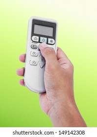 Hand holding a remote control of air conditioner on colour background