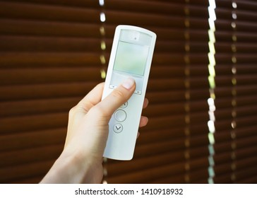 hand holding remote control to open wooden blinds