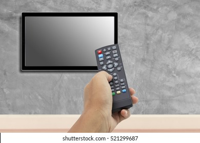 hand holding remote control  at television screen with concrete wall for background.