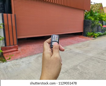 Hand holding the remote to open the sliding door.Remote control door.Electrical door.Automatic door.
