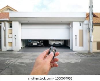 Hand holding the remote to open the sliding door.Remote control door.Electrical door.Automatic door.