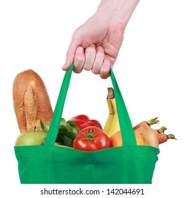 Hand holding a reusable shopping bag filled with fruits and vegetables, isolated on white