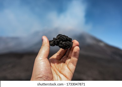 hand holding rock formation at the top of mount Etna, Sicily, Italy