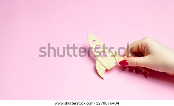 Hand holding a rocket on a pink background. Concept of startup or crowdfunding. Popularization of popular science and technology, passion for rockets and space travels. development of space tourism