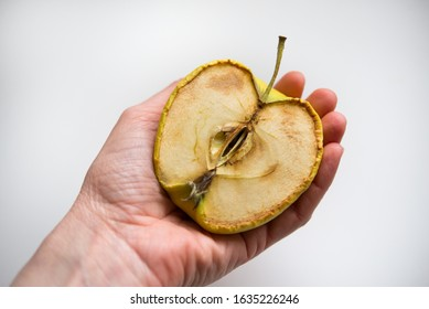 Hand holding a rotten apple