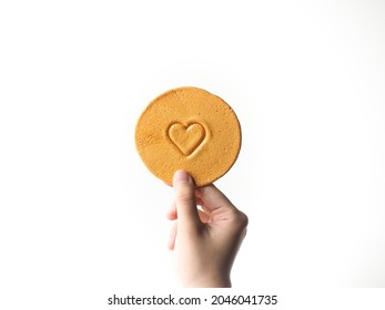 hand holding round honeycomb toffee sugar candy with mini heart shape on white background