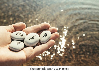 Hand holding rune stones with black symbols on for seeing the future, beautiful outdoor sunny bokeh sea water on the background.