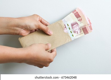 hand holding rupiah Indonesian money on brown envelope