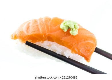 Hand holding salmon sushi and wasabi with chopsticks on white ba