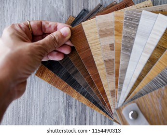 Hand holding sample stack of PVC vinyl wood planks shading for new home or floor renovation design idea