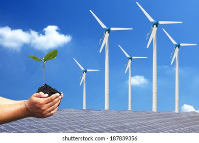 Hand holding seedling background solar cells and wind turbines. natural Energy