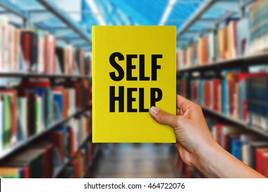 A hand holding 'Self-Help' book.