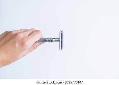 hand holding shaving  metal and stainless razor isolated on white background. Zero waste and sustainable product for shaving