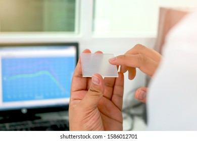 Hand holding sheet PMMA acrylic plate to apply sunscreen for measurement of radiation protection of cosmetic by using ultraviolet meter, with UV absorber spectrum as blue background, in vitro test lab