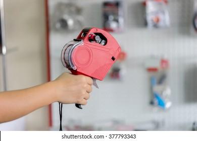 Hand holding shop pricing gun