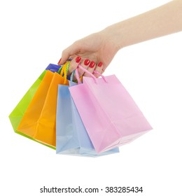 Hand holding shopping bags isolated over white background