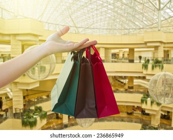 hand holding  shopping bags in  shopping mall
