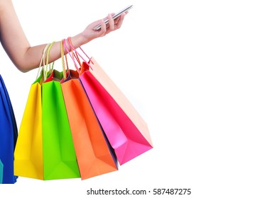 Hand holding shopping bags and mobile smart phone with blank space
