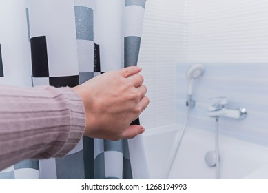 Hand holding shower curtain in white bathroom.