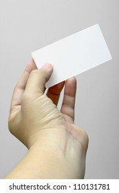 Hand holding and showing a blank business card.