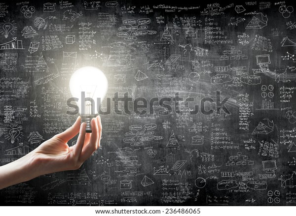 mano sosteniendo o mostrando una bombilla en frente del concepto de idea de negocio en la pared de la parte trasera de la tierra