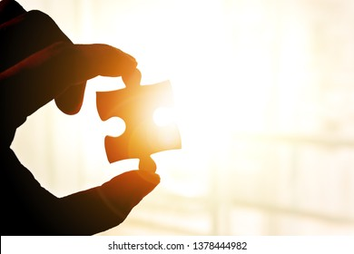 Hand holding and showing piece of jigsaw puzzle against sunrise effect.Fulfill and  fix the problem of incomplete.Business solutions for success and strategy concept.