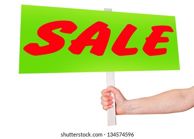 Hand holding sign with inscription SALE