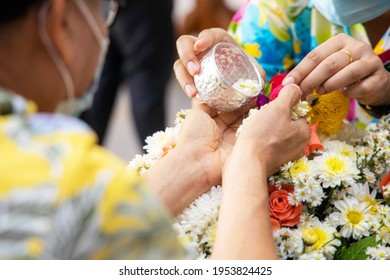 Hand holding silver bowl to pouring scented water on the hands of revered elders and ask for blessing in songkran day with COVID-19 is thought to spread. Thai holiday songkran festival new normal.