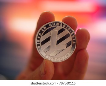 Hand holding silver litecoin LTC coin on colorful background, closeup. Blockchain crypto investment concept.