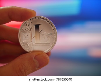 Hand holding silver litecoin LTC coin on colorful background, closeup. Blockchain investment concept.