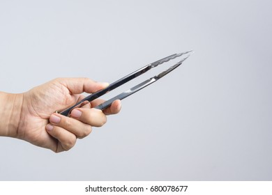 Hand holding silver serving kitchen tongs for picking food on white background