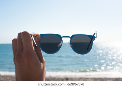 Hand holding silver sunglasses at the beach in front of the sea