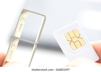 Hand holding sim card and sim card tray over smart phone in background