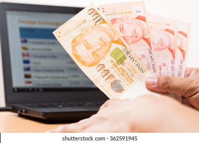 Hand holding Singapore dollar in office with computer screen showing foreign exchange table in background