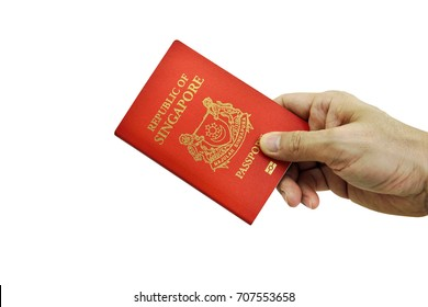 Hand holding Singapore Passport isolated on white background, selective focus. Clipping path included.