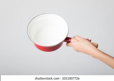 Hand holding a  single-handled pot.